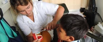 A young boy learns how to brush his teeth correctly with the help of a student doing a Dentistry internship abroad.